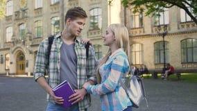 Jeunes mâle beau et femelle tenant l'université proche et parlant, étudiants clips vidéos