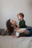 Jeunes mère et bébé dans des chandails de knit jouant sur le lit, concept Photos stock
