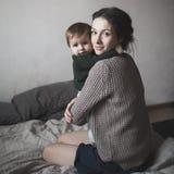 Jeunes mère et bébé dans des chandails de knit jouant sur le lit, concept Image stock