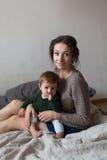 Jeunes mère et bébé dans des chandails de knit jouant sur le lit, concept Photos libres de droits