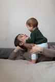 Jeunes mère et bébé dans des chandails de knit jouant sur le lit, concept Image libre de droits