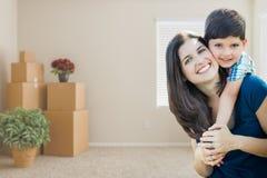 Jeunes mère et fils à l'intérieur de pièce vide avec les boîtes mobiles Photos stock
