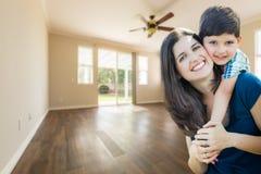 Jeunes mère et fils à l'intérieur de pièce vide avec les planchers en bois durs Images stock