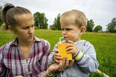 Jeunes mère et fils 1 3 ans sur la pelouse verte lait de consommation de garçon Images stock