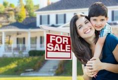 Jeunes mère et fils devant pour le signe et la maison de Real Estate de vente Photo libre de droits