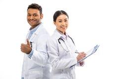 Jeunes médecins professionnels se tenant ensemble et faisant des gestes Photographie stock libre de droits