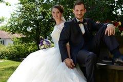 Jeunes ménages mariés frais se reposant sur un banc à un parc Photographie stock