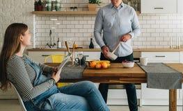 Jeunes ménages mariés heureux dans la cuisine L'homme se tient prêt la table de cuisine et la préparation de la femme enceinte de Image stock