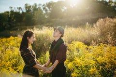 Jeunes mains de fixation de couples Dans le lever de soleil de nature Image stock