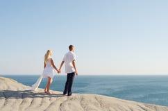 Jeunes mains de fixation de couples et regarder la mer Photos stock
