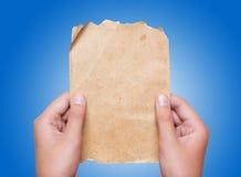 Jeunes mains femelles tenant la feuille de papier de vintage au-dessus du backgro bleu Images stock