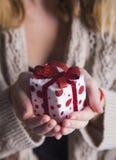 Jeunes mains femelles tenant le boîte-cadeau simple Image libre de droits