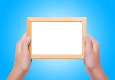 Jeunes mains femelles tenant le cadre de photo au-dessus du fond bleu Image libre de droits