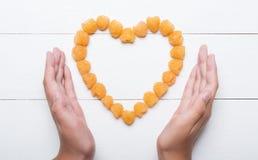 Jeunes mains jugeant le coeur fait de framboises jaunes Image libre de droits