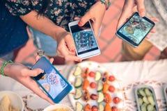 Jeunes mains prenant des photos avec des smartphones à Images stock