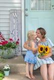 Jeunes maman et fille mignonnes sur le seuil avant en été image libre de droits