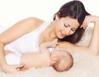 Jeunes maman heureuse et bébé se trouvant sur le lit Images stock