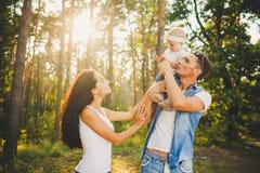 Jeunes maman, papa et fille élégants de famille une séance blonde an avec le père sur jouer d'épaules heureux et sourire, extérie Photographie stock