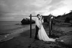Jeunes marié et jeune mariée de couples avec un bouquet le soir sur le Th Photographie stock