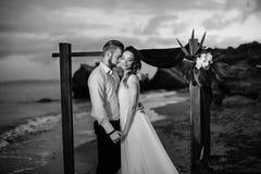 Jeunes marié et jeune mariée de couples avec un bouquet le soir sur le Th Images stock