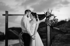 Jeunes marié et jeune mariée de couples avec un bouquet le soir sur le Th Image libre de droits