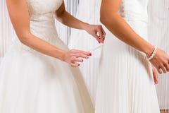 Jeunes mariées au montage de robe de mariage dans la boutique Image stock