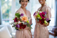 Jeunes mariées heureuses tenant le bouquet Images stock