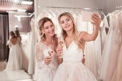 Jeunes mariées positives joyeuses prenant un selfie ensemble photo libre de droits