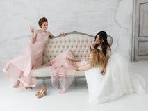 Jeunes mariées prenant le selfie tout en jouant sur le sofa et buvant du champagne Images libres de droits