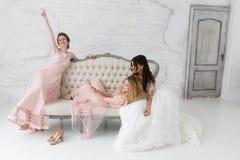 Jeunes mariées prenant le selfie tout en jouant sur le sofa et buvant du champagne Photos stock