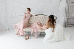 Jeunes mariées prenant le selfie tout en jouant sur le sofa et buvant du champagne Image libre de droits