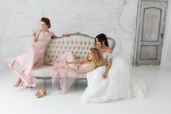 Jeunes mariées prenant le selfie tout en jouant sur le sofa et buvant du champagne Photo stock