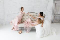 Jeunes mariées prenant le selfie tout en jouant sur le sofa et buvant du champagne Images stock