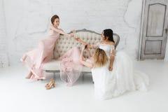 Jeunes mariées prenant le selfie tout en jouant sur le sofa et buvant du champagne Photographie stock