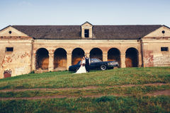 Jeunes mariés à côté de la rétro voiture Images libres de droits