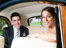 Jeunes mariés à l'intérieur d'une belle voiture classique photos libres de droits