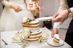 Jeunes mariés à la réception de mariage coupant le gâteau de mariage avec des fleurs Image libre de droits