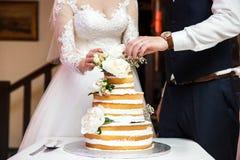 Jeunes mariés à la réception de mariage coupant le gâteau de mariage avec des fleurs Photographie stock