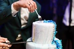 Jeunes mariés à la réception de mariage coupant le gâteau de mariage avec des fleurs Image stock