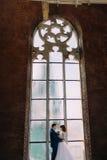 Jeunes mariés élégants heureux se tenant devant la vieille cathédrale gothique arquée de fenêtre Photos libres de droits