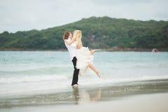 Jeunes mariés étreignant à la mer couples dans l'amour sur la plage abandonnée Image libre de droits