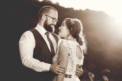 Jeunes mariés étreignant au coucher du soleil noir et blanc Photographie stock