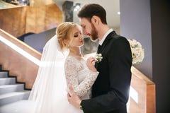 Jeunes mariés étreignant et embrassant tout en se tenant sur les escaliers Image stock