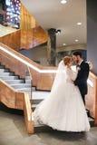 Jeunes mariés étreignant et embrassant tout en se tenant sur les escaliers Photographie stock libre de droits