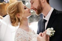 Jeunes mariés étreignant et embrassant tout en se tenant sur les escaliers Images stock