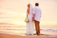 Jeunes mariés, appréciant le coucher du soleil étonnant sur un beau tropical Images stock