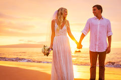 Jeunes mariés, appréciant le coucher du soleil étonnant sur un beau tropical Photographie stock