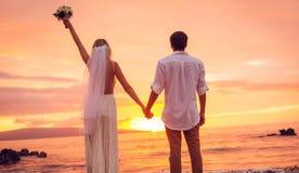 Jeunes mariés, appréciant le coucher du soleil étonnant sur un beau tropical Photographie stock libre de droits