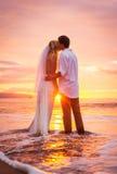 Jeunes mariés, appréciant le coucher du soleil étonnant sur un beau tropical Photo stock