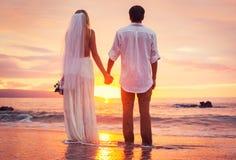 Jeunes mariés, appréciant le coucher du soleil étonnant sur une belle plage tropicale Photographie stock